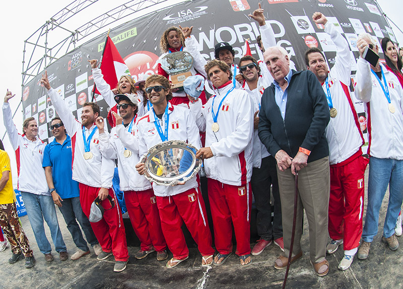Team Peru, the Claro ISA 50th Anniversary World Surfing Games Team Champions, holding the Fernando Aguerre World Team Trophy, joined by the first ISA President in 1964, Eduardo Arena. Photo: ISA/Rommel Gonzales